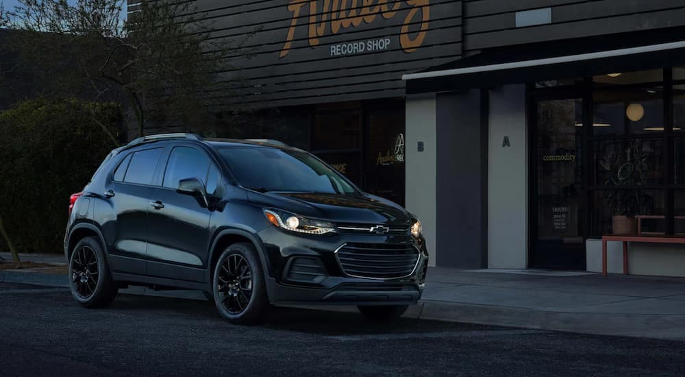 A black 2021 Chevy Trax is parked in front of a record store at dusk.