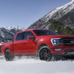 A red 2021 Ford F-150 is driving through the snow after winning a 2021 Ford F-150 vs 2021 Nissan Titan comparison.