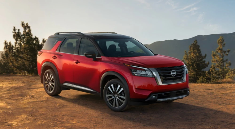 A red 2022 Nissan Pathfinder is shown angled to the right parked on dirt.
