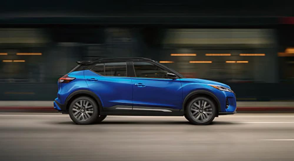 A blue 2022 Nissan Kicks is shown from the side driving through a city.