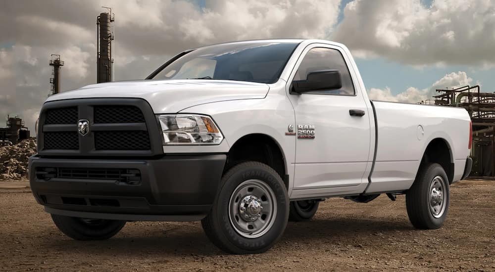 A white 2016 Ram 2500 is parked on dirt in front of a construction site.
