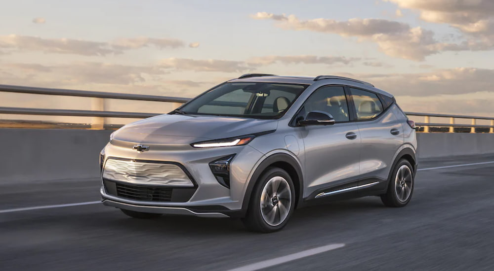 A silver 2022 Chevy Bolt EUV is shown from the side driving over a bridge at sunset after leaving an electric car dealer.