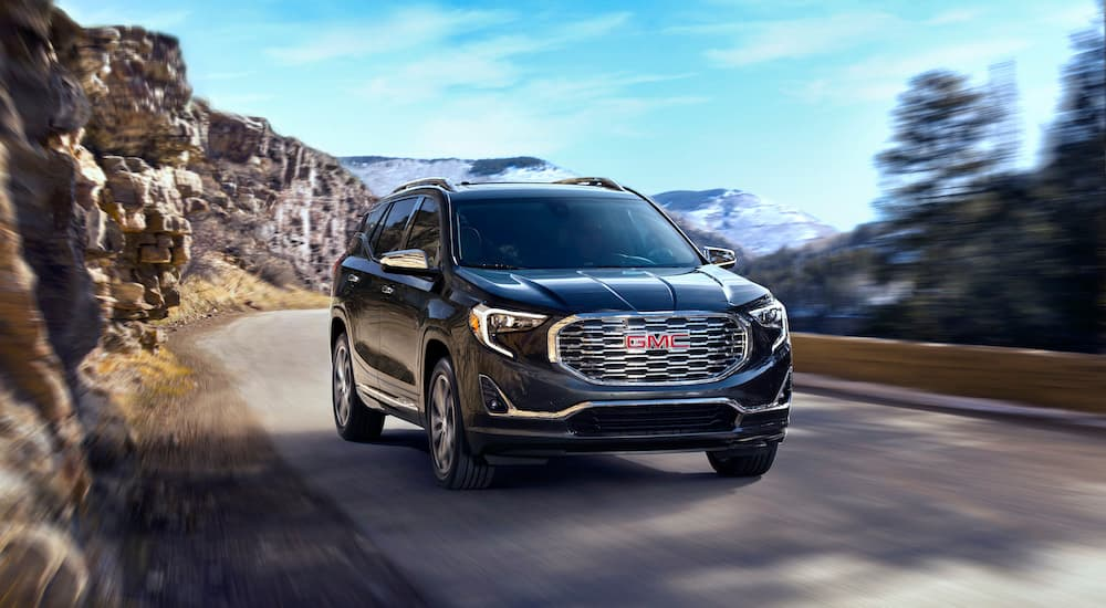 A black 2020 GMC Terrain is shown driving from the front.