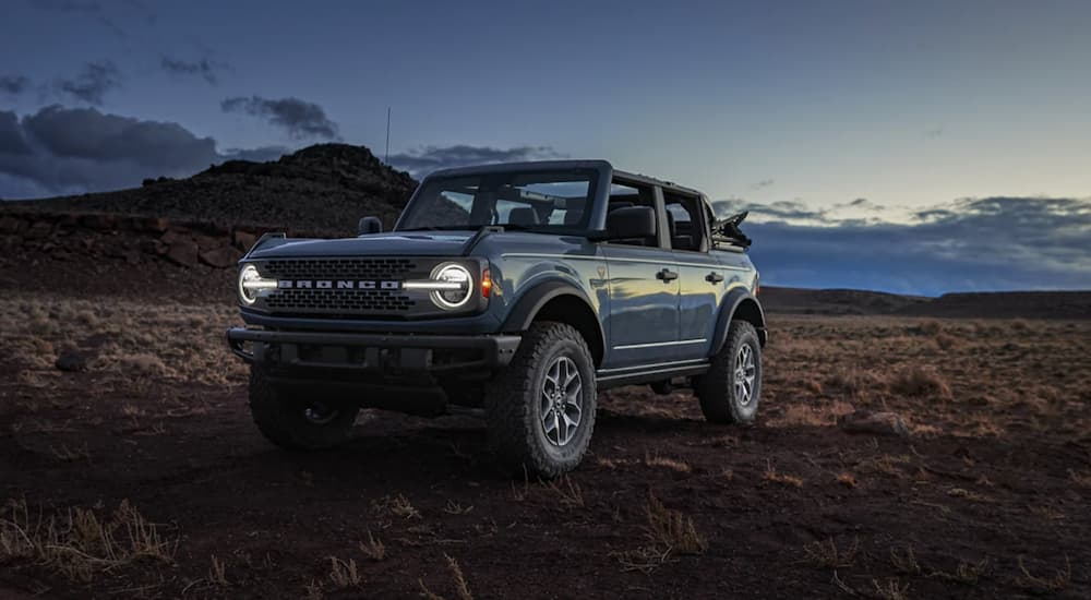 A blue 2021 Ford Bronco is shown parked in a desert at dusk.