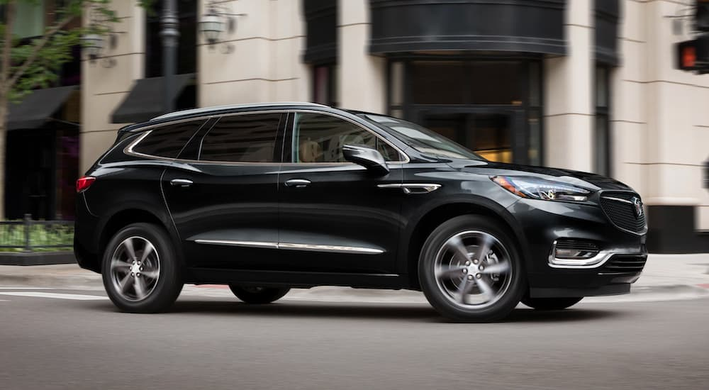A black 2021 Buick Enclave is shown driving through a city.
