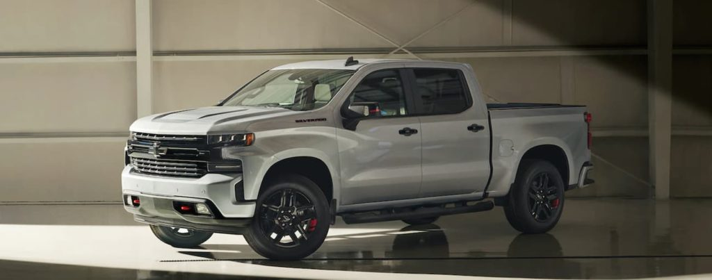 A silver 2021 Chevy Silverado 1500 is parked in a modern gallery after winning a 2021 Chevy Silverado vs 2021 Ford F-150 comparison.