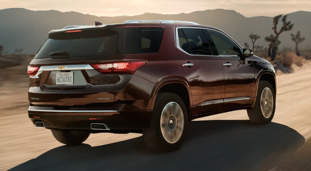 A maroon 2021 Chevy Traverse is shown from the back driving on a desert road.