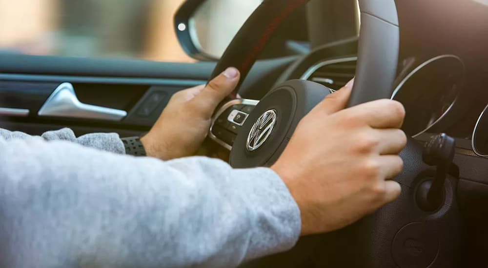 A close up shows hands on the steering wheel of a 2022 Volkswagen Golf GTI.