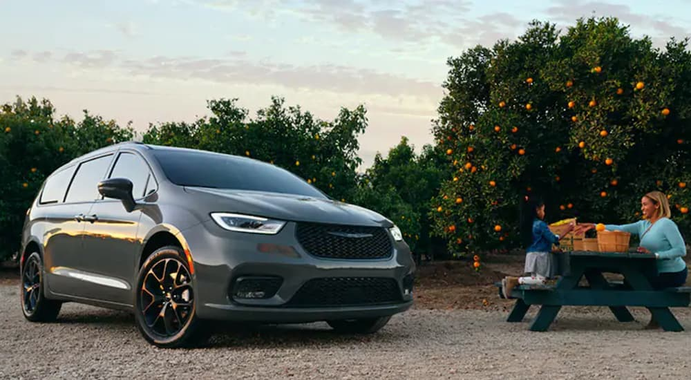 A grey 2020 used Chrysler Pacifica Hybrid is parked next to a picnic bench.