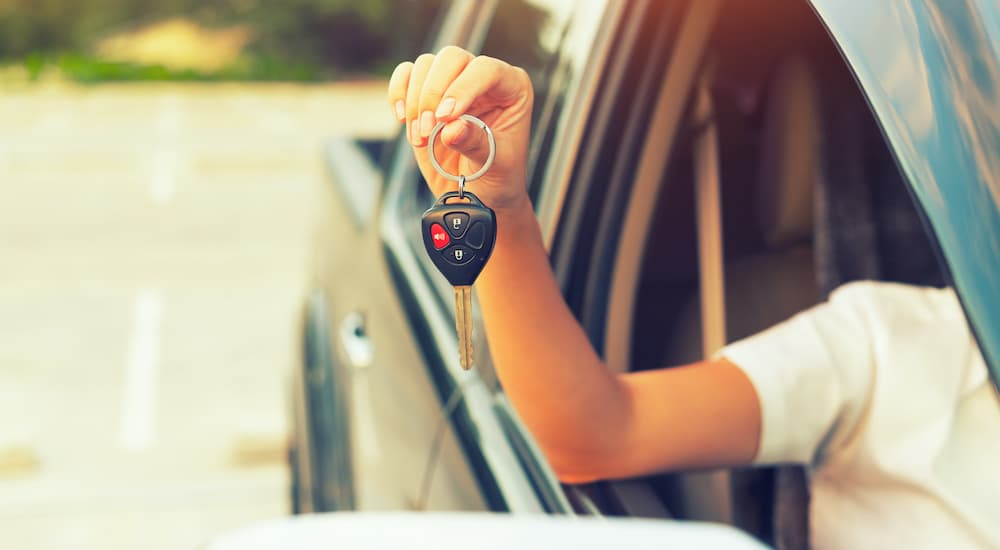 A person is holding out a set of car keys through a passenger window.