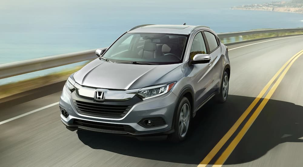 A grey 2021 Honda HR-V EX-L is shown from the fornt driving next to an ocean.