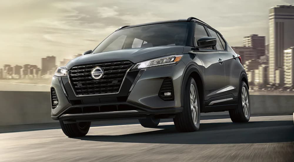 A grey 2021 Nissan Kicks is shown from the front driving through a city after winning a 2021 Nissan Kicks vs 2021 Honda HR-V comparison.