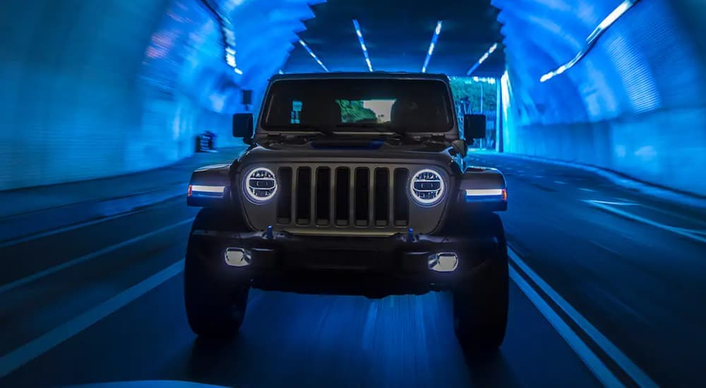 A silver 2021 Jeep Wrangler 4xe is shown from the front driving through a tunnel.