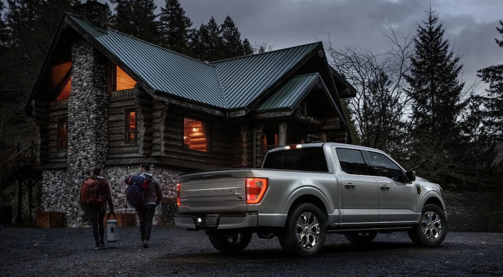 A silver 2021 Ford F-150 Platinum is shown from the rear parked near a cabin at night.