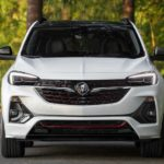 A white 2022 Buick Encore GC is shown from the front parked in front of a forest.
